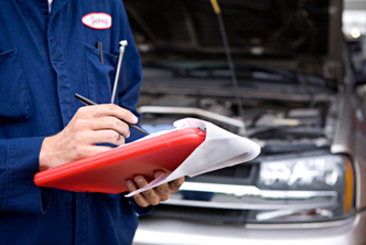 Photo of ASE Certified Technician With Vehicle Inspection Form